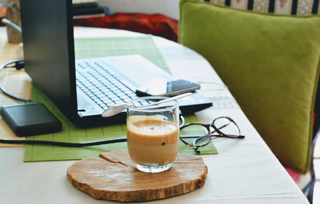 kawa na biurku przy laptopie